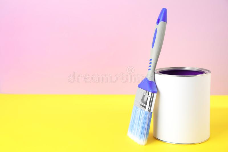 Blank can of paint with brush on table against color background. Space for text royalty free stock image