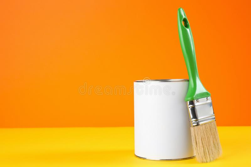 Blank can of paint with brush on table against color background. Space for text royalty free stock images
