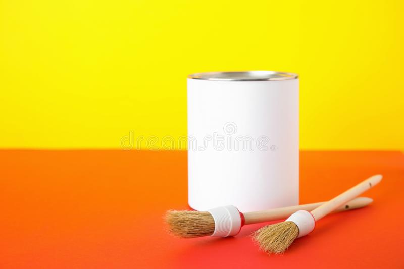 Blank can of paint with brushes on table against color background. Space for text royalty free stock image