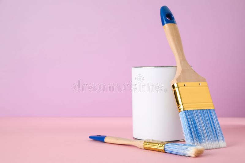 Blank can of paint with brushes on table against color background. Space for text stock photography
