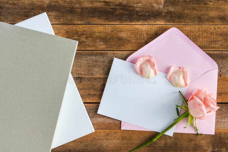 Blank card and pink envelope. Blank card decorated with beautiful pink rose on wooden table, top view stock photography