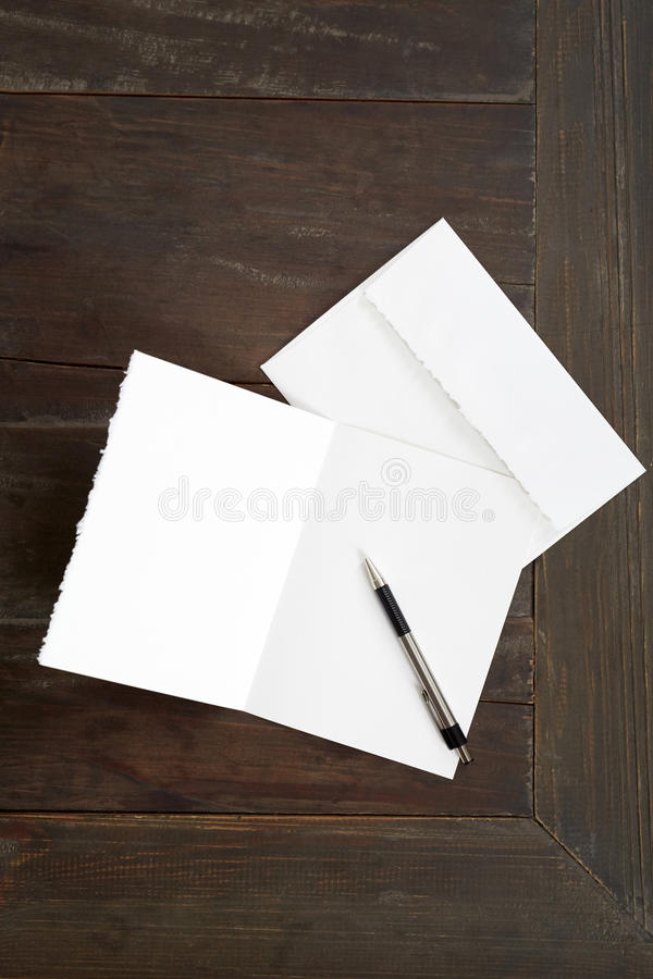 Blank card. A blank greeting card on a wood desk royalty free stock photo