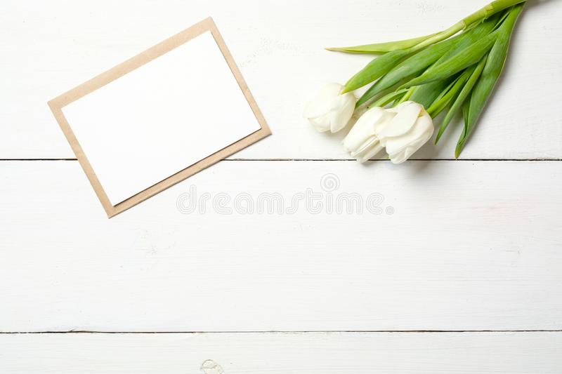 Blank card for invitation or congratulation with bunch of white tulips flowers on white wooden table. Vintage banner mockup for sp. Ring holidays, International stock photography