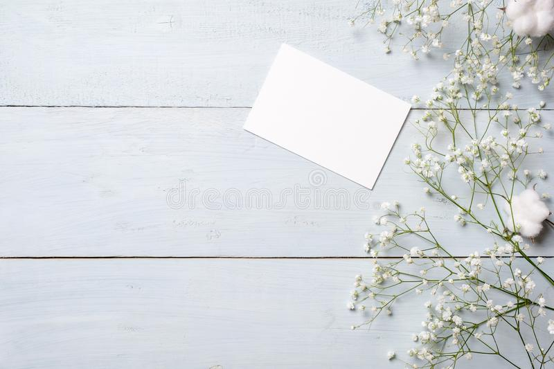 Blank card for invitation or congratulation, little gift box, bunch of gypsophila flowers on light blue wooden table. Banner mocku stock image