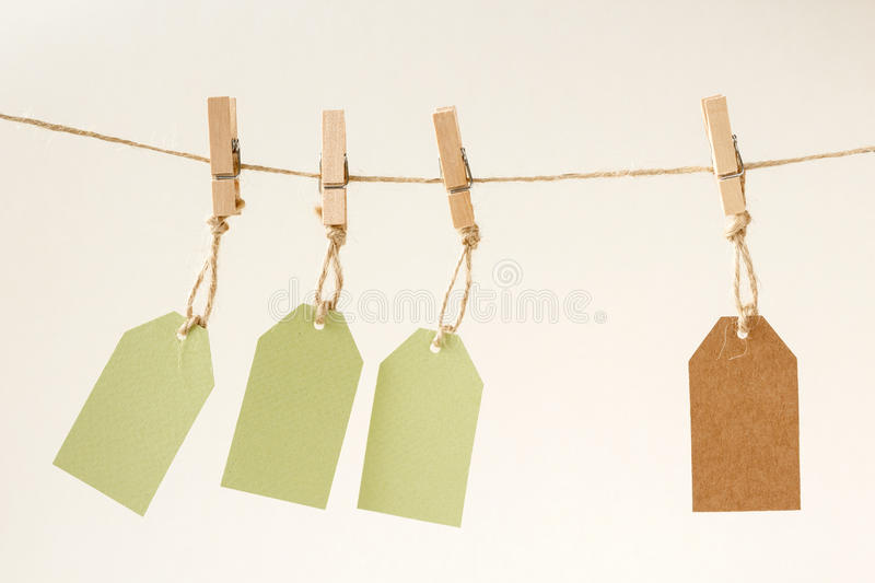 Blank cardboard price tags on a wooden clothespins. Three green and one brown blank cardboard price tags tied with jute twine, hanging on a clothes line with royalty free stock image