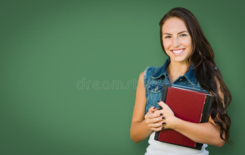 Blank Chalk Board Behind Mixed Race Young Girl Student Holds Books stock images