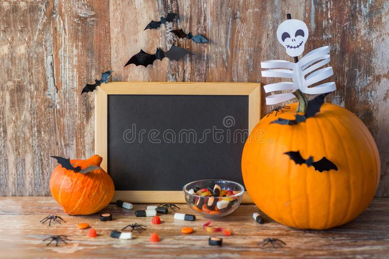 Blank chalkboard and halloween decorations. Holidays, school and party concept - halloween pumpkins, decorations with blank chalkboard on wooden boards royalty free stock photography