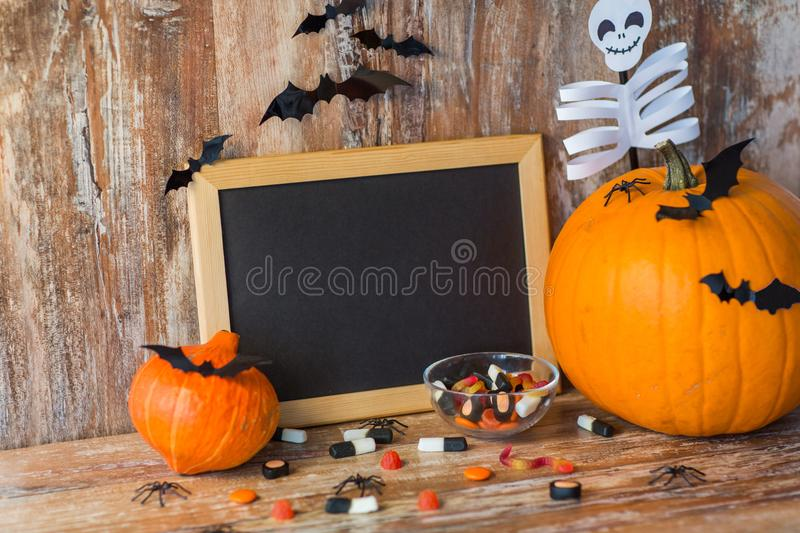 Blank chalkboard and halloween decorations. Holidays, school and party concept - halloween pumpkins, decorations with blank chalkboard on wooden boards stock photos