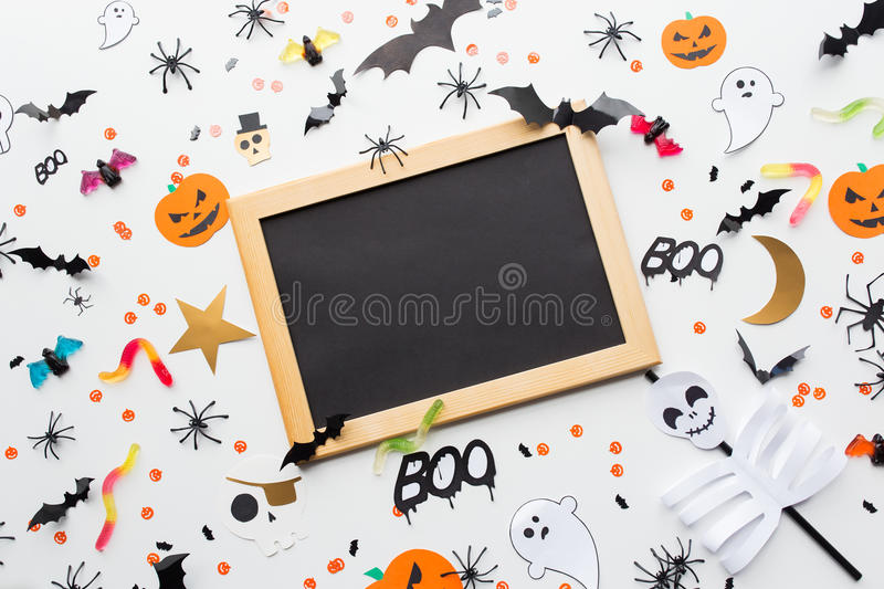 Blank chalkboard and halloween party decorations. Holidays, school and party concept - halloween decorations and candies with blank chalkboard over white stock images