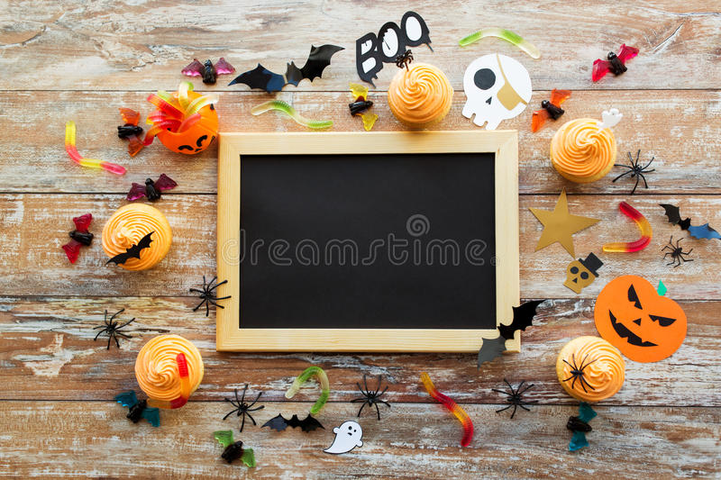 Blank chalkboard and halloween party decorations. Holidays, school and party concept - halloween decorations and treats with blank chalkboard on wooden boards royalty free stock photography