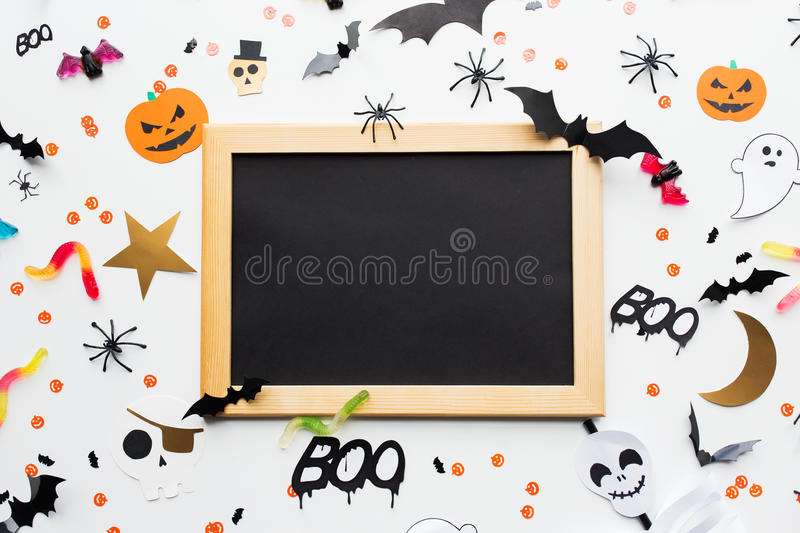 Blank chalkboard and halloween party decorations. Holidays, school and party concept - halloween decorations and candies with blank chalkboard over white royalty free stock photos