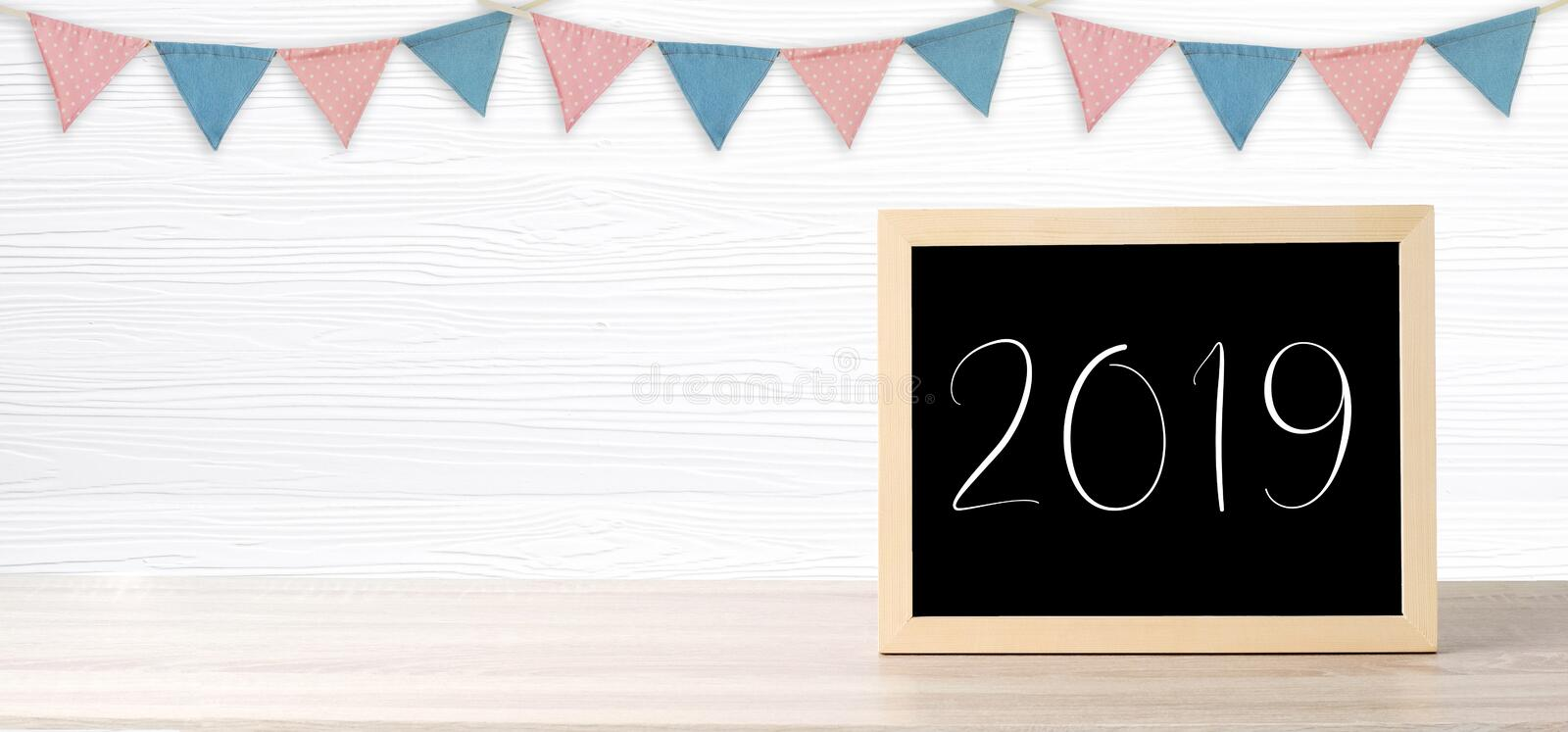 Blank chalkboard standing over colorful party flags hanging on w. Hite wood background with copy space for text, new year and festival card, banner stock photo