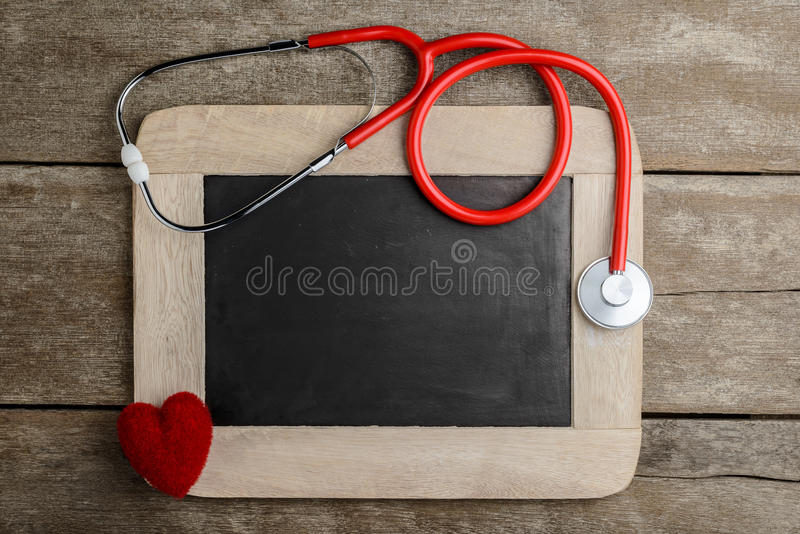 Blank chalkboard, stethoscope and red heart, health background c royalty free stock photo