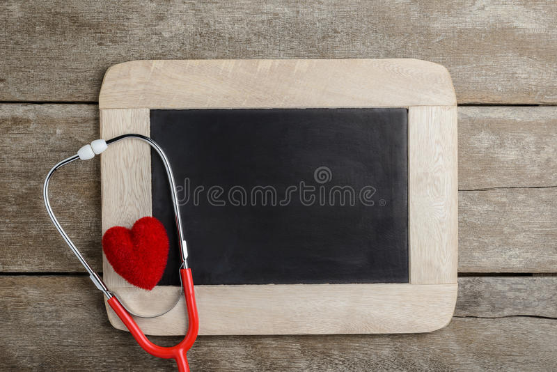 Blank chalkboard, stethoscope and red heart, health background c stock photo