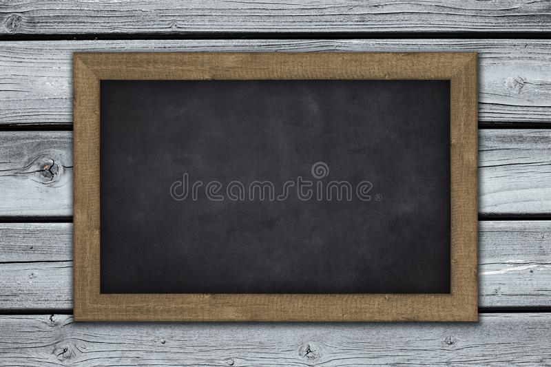 Blank  chalkboard on wooden wall background royalty free stock photography