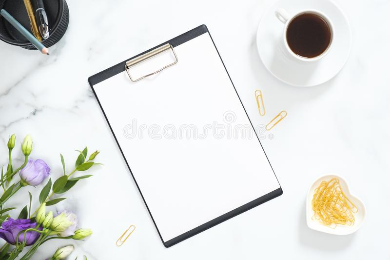 Blank clipboard mockup, golden stationery, flowers bouquet, coffee cup on marble background. Flat lay, top view minimalistic home. Office desk. Business concept royalty free stock photography
