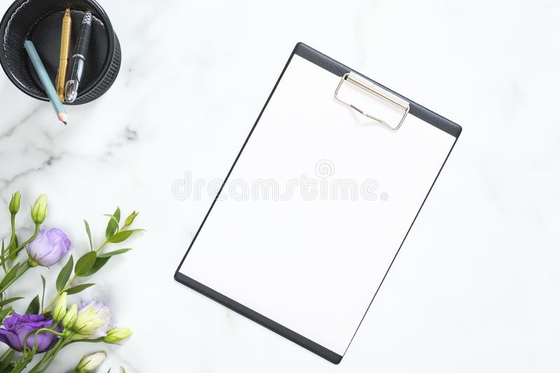 Blank clipboard mockup, stationery, flowers bouquet on marble background. Flat lay, top view minimalistic home office desk. Business concept stock images