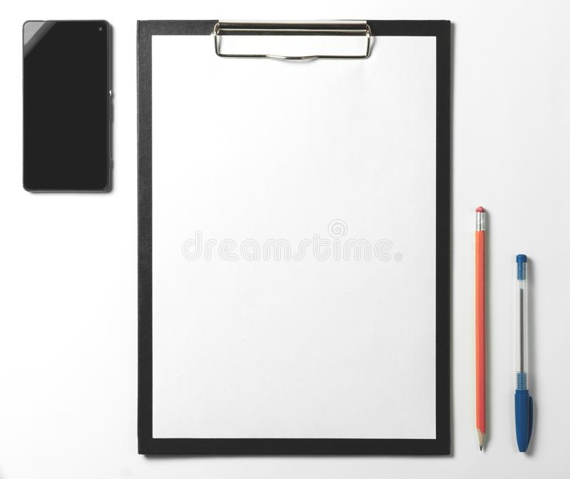 Blank clipboard, smartphone, pen and pencil on white background. royalty free stock photos