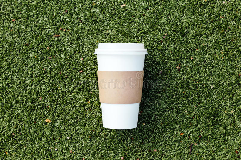 Blank coffee paper cup. On football field royalty free stock images