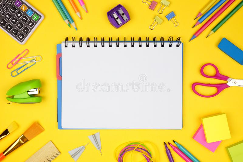 Blank notebook with school supplies frame against a yellow background. Back to school. Copy space. royalty free stock images