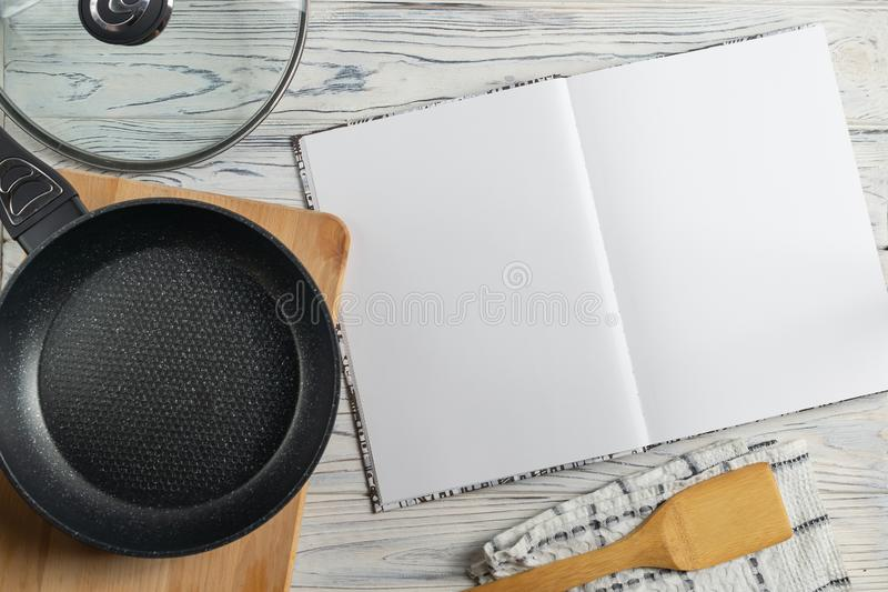 Blank cookbook for your tex, composition with frying pan on wooden table stock images