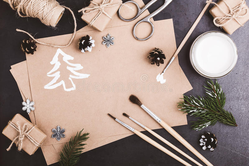 Blank of craft paper, paints and brushes on blue table with copy. Space for greeting text viewed from above, Christmas holiday theme royalty free stock image