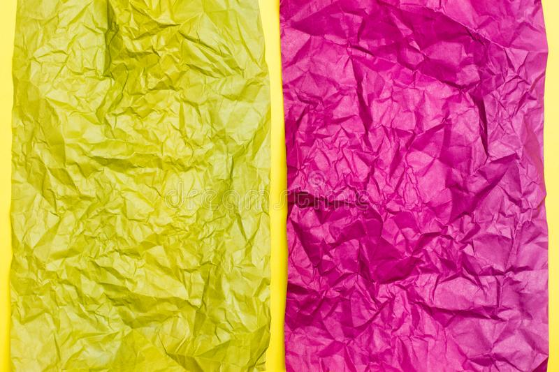 Blank crumpled purple and yellow sheets of colored paper on a yellow cardboard background. Textural motley background stock photography