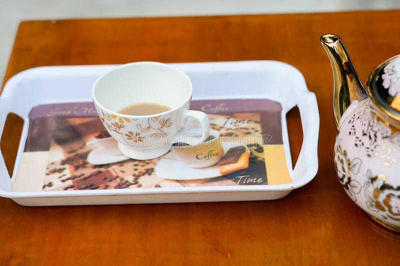 Blank cup on a tray with a kettle. royalty free stock image