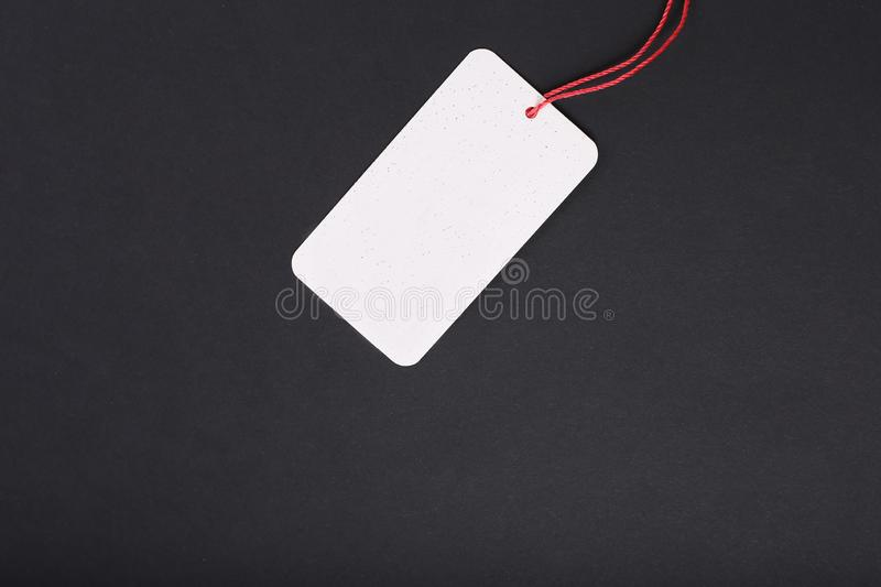 Blank decorative cardboard tag with red twine tie on black background stock images