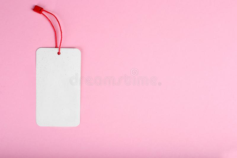 Blank decorative cardboard tag with red twine tie, on pink background stock photography