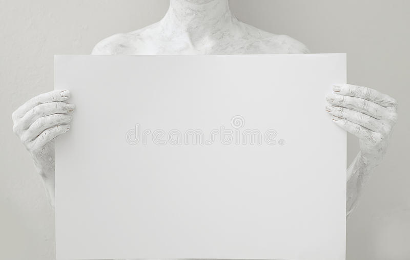 Blank design poster template. Woman covered with white paint holding a paper. Focus on hands royalty free stock photography