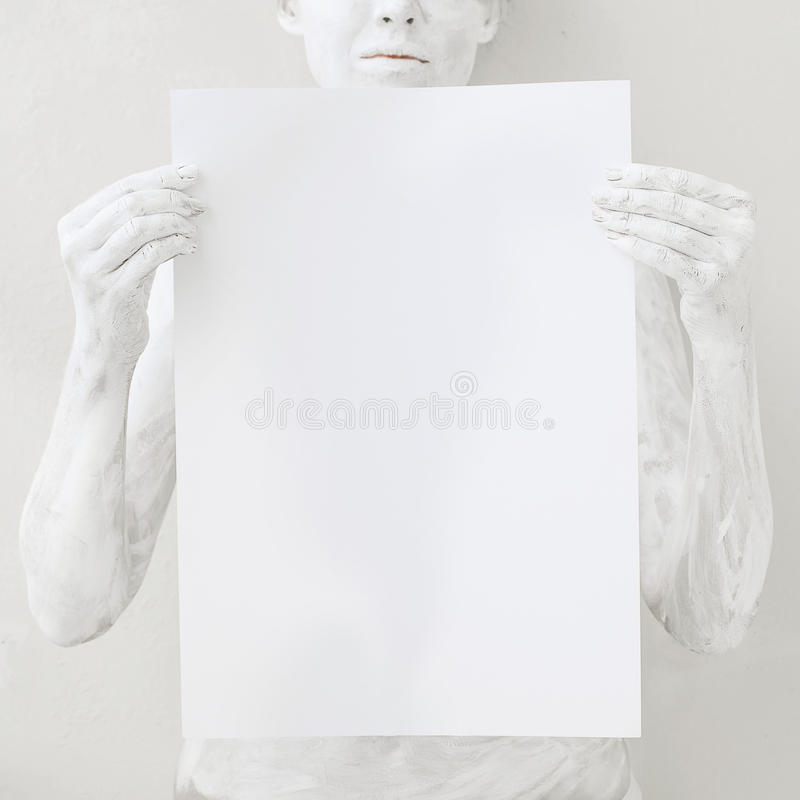 Blank design poster template. Woman covered with white paint holding a paper. Focus on hands stock photo