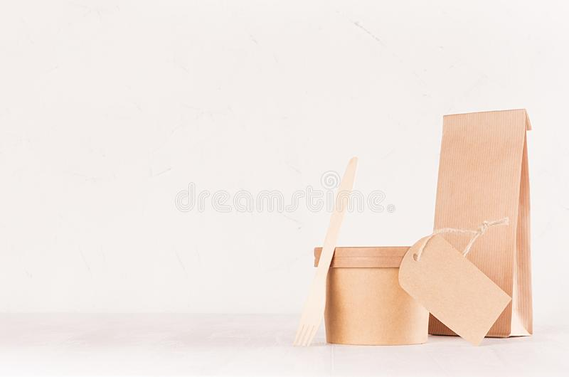 Blank different cardboard packaging for fast food - bag, cutlery, box, label of kraft paper on white wood shelf, copy space. Blank different cardboard packaging stock image