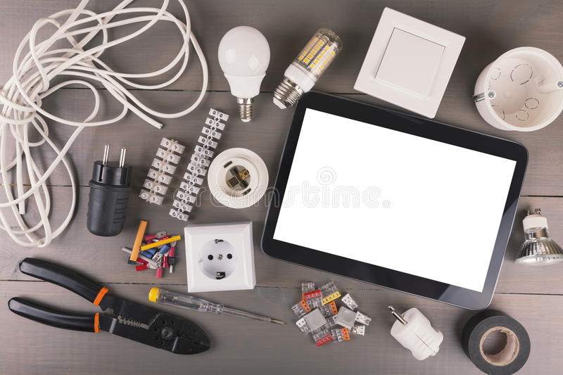 Blank digital tablet with electrical tools and equipment on wood. Blank digital tablet with electrical tools and equipment on gray wooden table stock photography