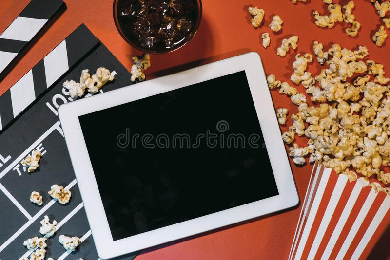 Blank digital tablet, popcorn, filmstrip, cinema and movie online streaming concept stock images