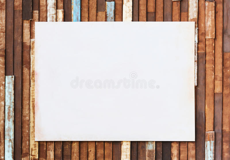 Blank dirty poster paper on old wooden wall. For advertisement stock photos