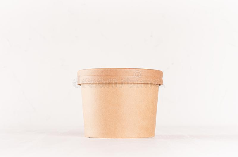 Blank disposable brown paper box for takeaway food - soup, salad, ice cream on white wood shelf closeup, mockup food packaging. Blank disposable brown paper box stock images