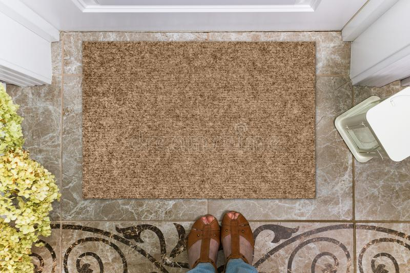 Blank doormat before the door in the hall. Mat on ceramic floor, flowers and shoes. Welcome home, product Mockup royalty free stock photos