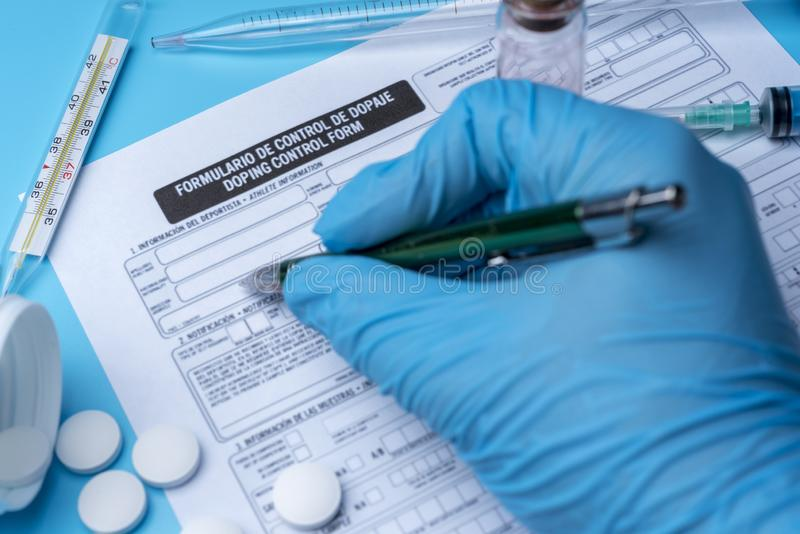 A gloved hand writes on a doping control form. royalty free stock image