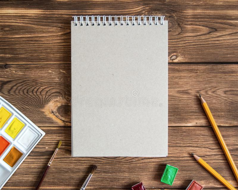 Blank drawing pad with pencils and paints on a wooden background stock image