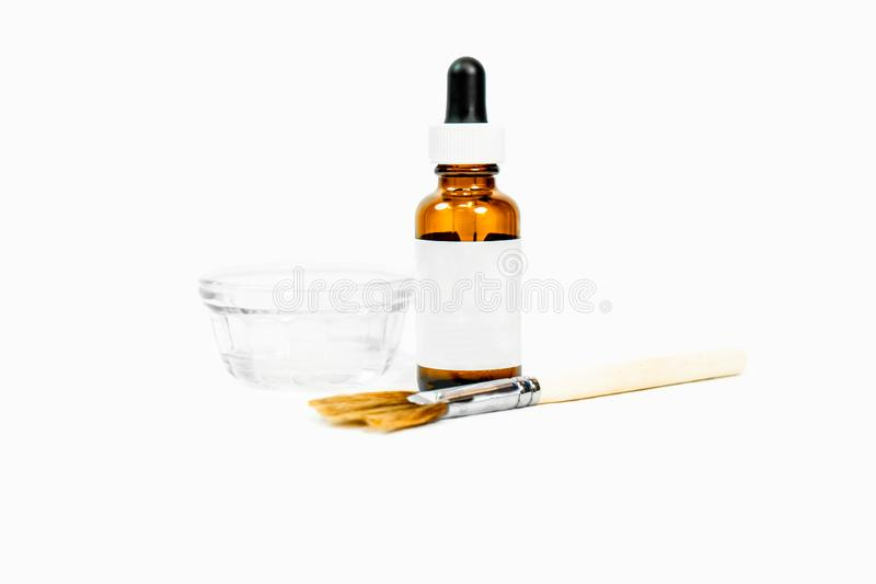 Blank drip bottle for cosmetic chemical peel formula, with dish and applicator makeup brush, for beauty treatments, with white bla stock photos
