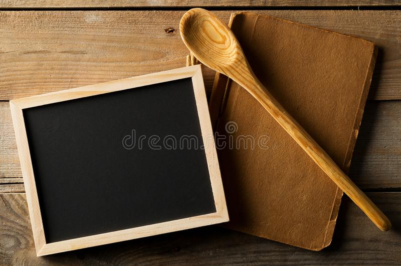 Blank, empty, black chalkboard with wooden cooking spoon and old recipe book flat lay from above on black wooden table. With copy space royalty free stock photo