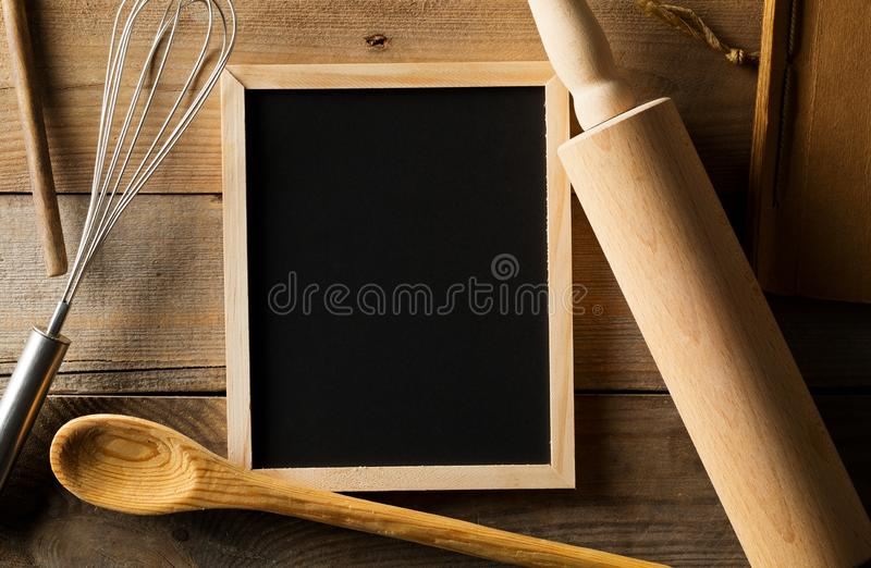 Blank, empty, black chalkboard with wooden rolling pin, wire whisk and recipe book flat lay from above on brown wooden table stock photography