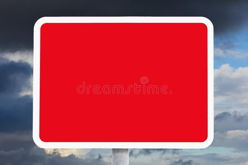 Road sign copy space danger background template. Blank or empty red and white british road sign in front of dark clouds, indicating a safety hazard, risk, danger royalty free stock images