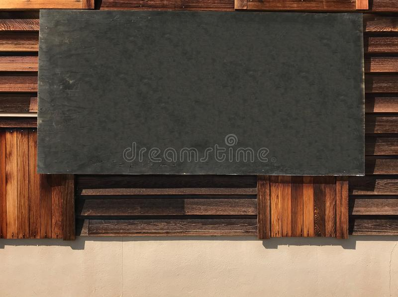 Blank empty rustic vintage wooden black board hanging on the wooden wall, copy space ready for message, image or texts stock photo