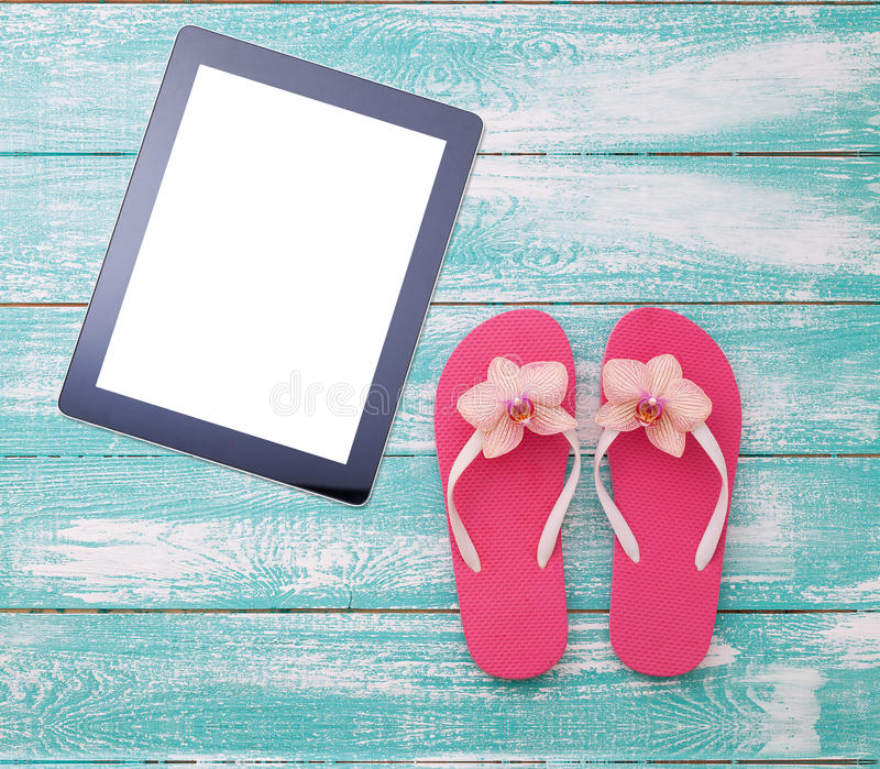 Blank empty tablet computer on beach. Trendy summer accessories on wooden background pool. Flip-flops on beach. Tropical flower or. Chid. Flat mock up for design stock images