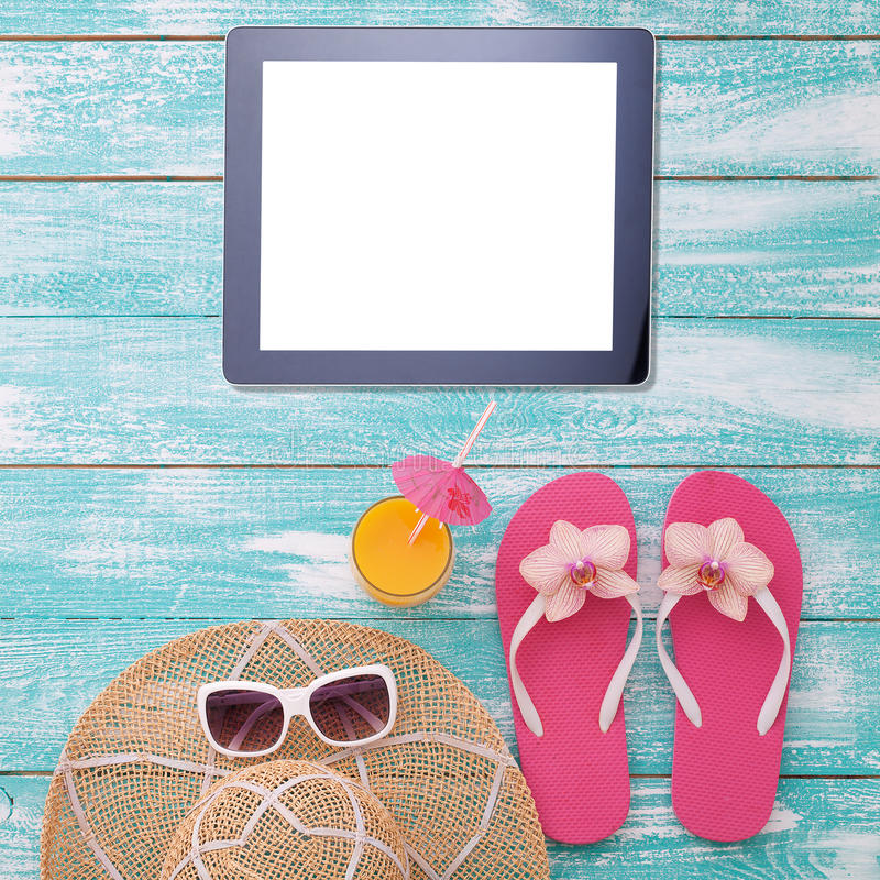 Blank empty tablet computer on beach. Trendy summer accessories on wooden background pool. Sunglasses, orange juice and royalty free stock photo