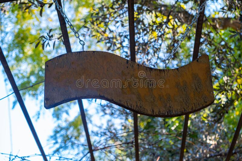 Blank empty wood sign hanging of a metal structure, blue sky and trees background stock photography
