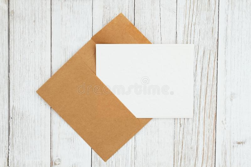 Blank envelope with greeting card on weathered whitewash textured wood background stock image