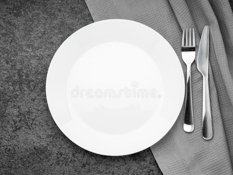 Blank flat white plate, fork on dark gray stone concrete table, top view. Mock up, copy space royalty free stock images